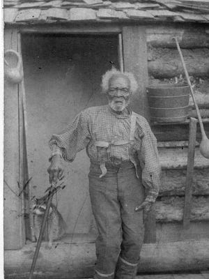 This picture of Jerry Akin appeared in the Piedmont newspaper in 1985. Akin is pictured in front of his log cabin. Note the raccoon in the doorway.