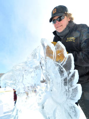 Carver Jon Mykkanen, of Ishpeming, MI, carves an ice sculpture during the 2014 Winter Fest at The 400 Block in downtown Wausau.