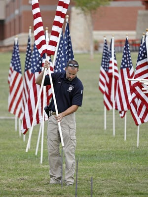 Lubbock police officer Kyle Purdue place a flag in the ground for a 9/11 memorial, Monday, Sept. 10, 2018, at Kastman Park in Lubbock, Texas.