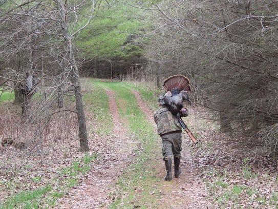 Tim Eisele of Madison carries a wild turkey he shot