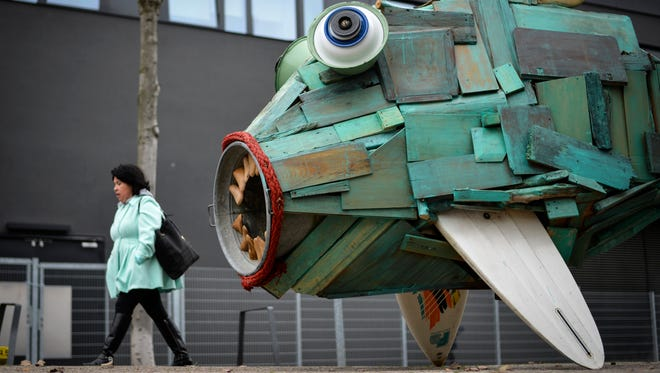 A woman walks past the sculpture 'Watercreature' created from flotsam by youth culture project IYouWe during the UN Climate Change Conference COP23.