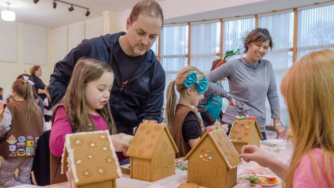 Tom Gostinger, of Kimball Township, decorates a gingerbread house with his daughter Allie, 7, Sunday, Dec. 4, at the Girl Scouts of Southeastern Michigan Port Huron Service Center.