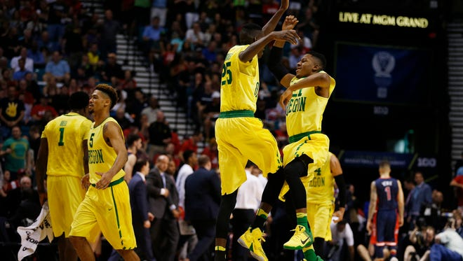 Oregon guard Kendall Small, right, and forward Chris Boucher (25) jump into the air in celebration during the first half of an NCAA college basketball game against Arizona in the semifinal round of the Pac-12 men's tournament Friday, March 11, 2016, in Las Vegas.