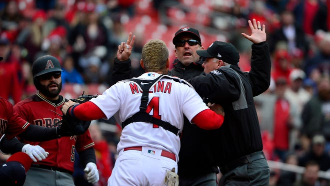 Apr 8, 2018; St. Louis, MO, USA; Arizona Diamondbacks manager Torey Lovullo (17) and St. Louis Cardinals catcher Yadier Molina (4) exchange words as umpire Tim Timmons (95) attempts to separate them during the second inning at Busch Stadium. Lovullo was ejected from the game. Mandatory Credit: Jeff Curry-USA TODAY Sports