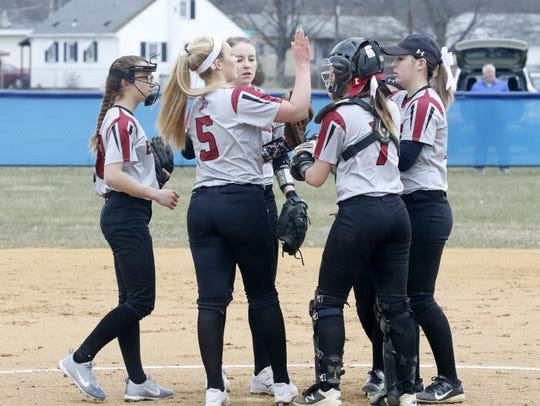 Bella Reese (5) huddles with her teammates during a