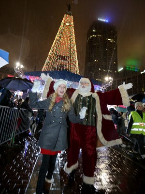 Lane Stark and Santa Claus waved to the thousands of people who showed up on Monument Circle in Downtown Indianapolis for the Circle of Lights celebration Friday, Nov. 27, 2015. Lane, 11, flipped the switch to turn on the lights after winning the Carson's Coloring Contest.