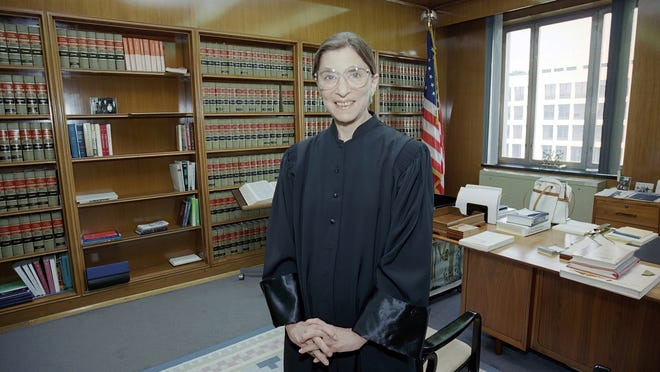 In this Aug. 3, 1993, file photo, then-Judge Ruth Bader Ginsburg poses in her robe in her office at U.S. District Court in Washington.