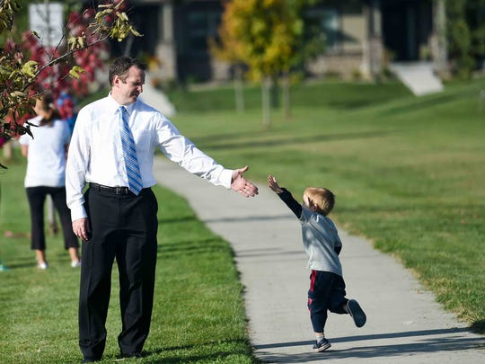 Ankeny school board member Dustin Graber and his son, Noah, 3, play as they wait for the Prairie Dog Dash at Prairie Trail Elementary School in 2015.