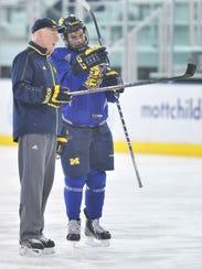 Red Berenson talks with forward Alex Kile at Michigan