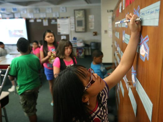 Fourth grade student Joemy Gonzalez practices writing a tweet during class at Northaven Elementary School in Jeffersonville, Ind. Northaven teachers are working to help students become better digital citizens by having them write out tweets before they post them on Twitter and teaching them about safe practices on the social media app. Aug. 4, 2014.