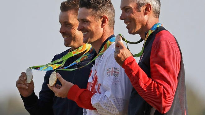 From Aug. 14, 2016, from left are silver medalist Henrik Stenson, of Sweden; gold medalist Justin Rose, of Britain; and bronze medalist Matt Kuchar, of the United States, after the final round of the men's golf event at the Summer Olympics in Rio de Janeiro, Brazil. Unlike other Olympic sports, the postponement to 2021 was little more than an inconvenience in golf.