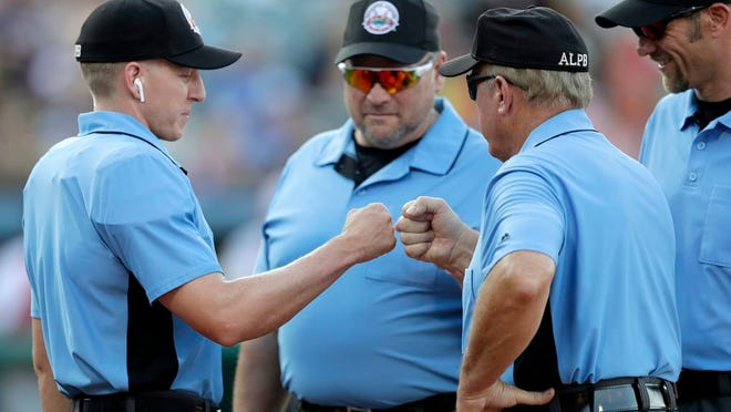 Home plate umpire Brian deBrauwere, left, huddles with officials while wearing an earpiece connected to a ball and strikes calling system prior to the start of the Atlantic League All-Star minor league baseball game, Wednesday, July 10, 2019, in York, Pa.