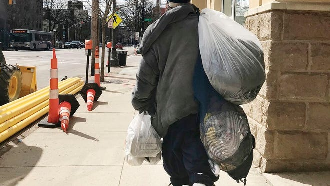 A homeless man carries his possessions along North High Street last year.