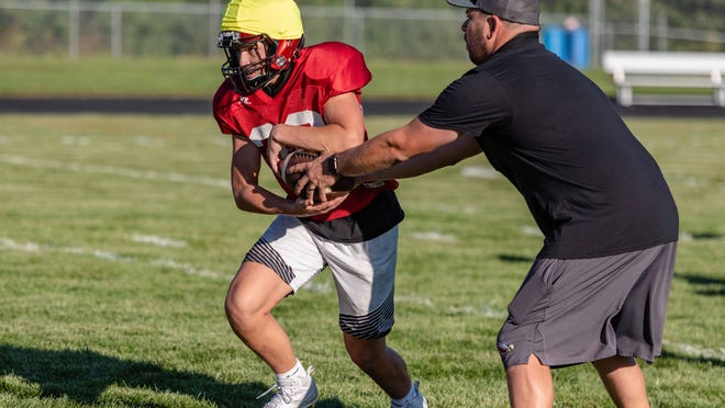 Southern Boone head coach Trent Tracy hands off the football to Jacob Bowles during a drill on Aug. 20.