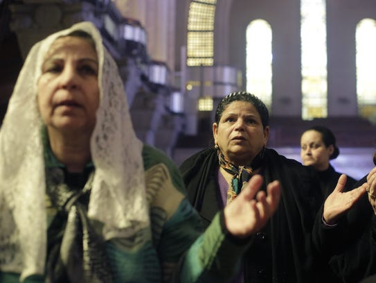 Women pray during a Mass led by Pope Tawadros II, the
