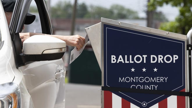 FILE - In this May 27, 2020, file photo, a voter drops off their mail-in ballot prior to the primary election, in Willow Grove, Pa. The civic ritual of casting a ballot has been disrupted by a global pandemic and dramatically animated by social unrest. And If the results of a frustrating, chaotic primary in Georgia are a measure, the notion of democracy itself will also be on the ballot in the November election. Congress is now considering sending $3.6 billion to states to help facilitate safe and fair elections as part of another round of relief funds to recover from the coronavirus pandemic. (AP Photo/Matt Rourke, File)