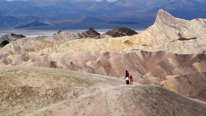 In this 2010 file photo, tourists walk along a ridge at Death Valley National Park.