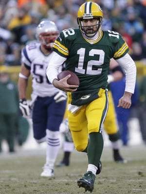Green Bay Packers quarterback Aaron Rodgers runs for a first down in the first half.