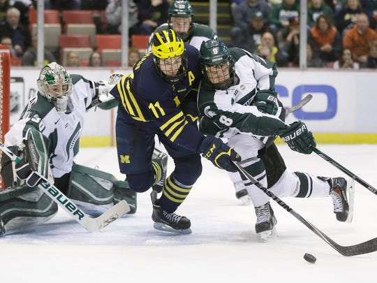 Michigan forward Zach Hyman (11) and Michigan State defenseman Josh Jacobs (8) chase the puck during the first period of an NCAA college hockey game Friday.