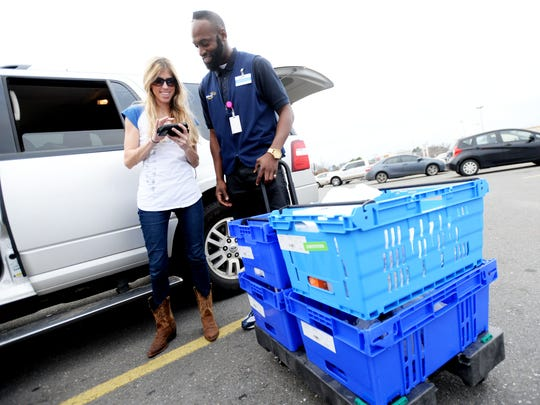 Melissa Gutman gets her groceries she ordered online from Eddie Dwayne Hamilton at the new Walmart pick up lane.