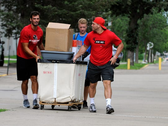 St. Cloud State University student volunteers help a freshman move his belongings into Sherburne Hall on Thursday, Aug. 18, 2016.