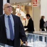 Jerry Amerosi greets a customer at Gerald Peters jewelers, one of three stores he owns in the Staten Island Mall in New York. Amerosi's three stores will be open on Thanksgiving, which is required by his leases with the mall.