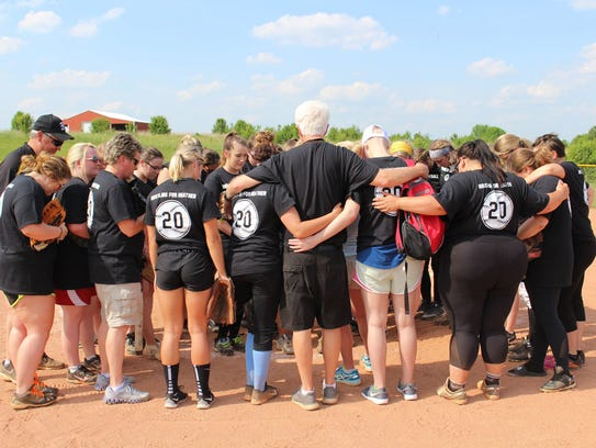 Heather Simmons (pink hat center) prays with her fellow