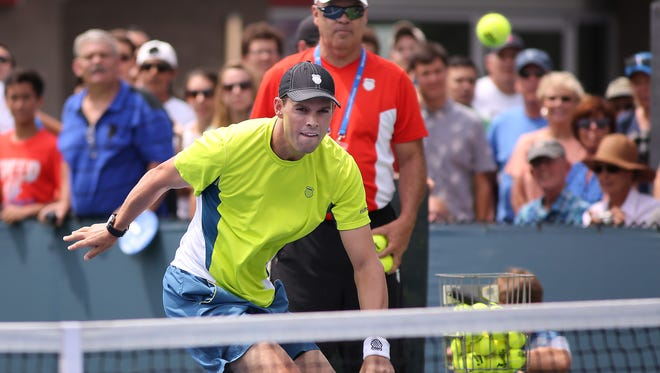 Doubles player Bob Bryan runs to hit the ball during the fan experience at the Western and Southern Open on Monday.