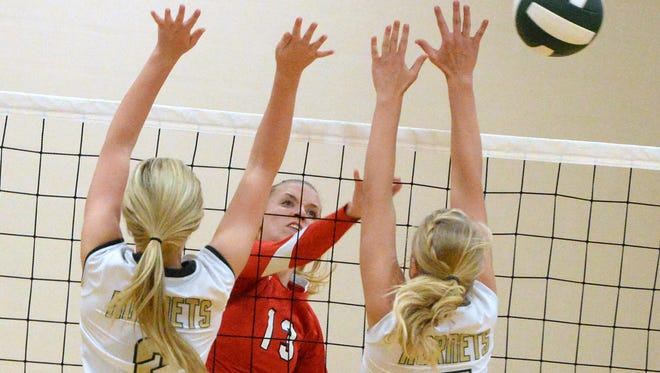 Riverheads' Mariah Clark sends the ball past Wilson Memorial's Lacy Arey and Jordan Poole during a volleyball match played in Fishersville on Thursday, Sept. 25, 2014.