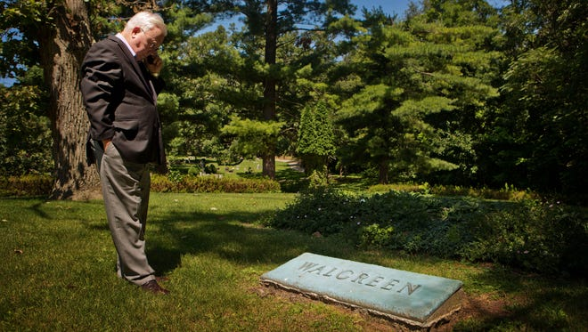 James Burke, mayor of Dixon, Ill., fields a phone call as he visits the grave of Charles R. Walgreen, the founder of the Walgreen Company, at the Oakwood Cemetery in Dixon on July 24.