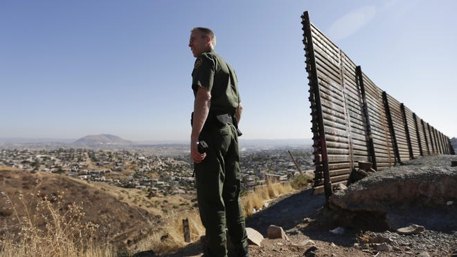 In this June 13, 2013 photo, U.S. Border Patrol agent Jerry Conlin looks out over Tijuana, Mexico, along the old border wall.