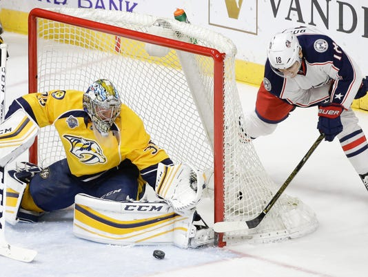 Nashville Predators goalie Pekka Rinne (35), of Finland, blocks a shot by Columbus Blue Jackets right wing Rene Bourque (18) in the second period of an NHL hockey game Saturday, March 26, 2016, in Nashville, Tenn. (AP Photo/Mark Humphrey)