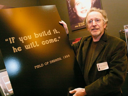 """Screenwriter Phil Alden Robinson poses beside a poster that bears a famous line from his film """"Field Of Dreams""""  at a cocktail reception honoring the screenwriters featured in the 79th Academy Awards marketing campaign at the """"Meet the Oscars"""" exhibition space at the Hollywood & Highland complex on February 13, 2007."""