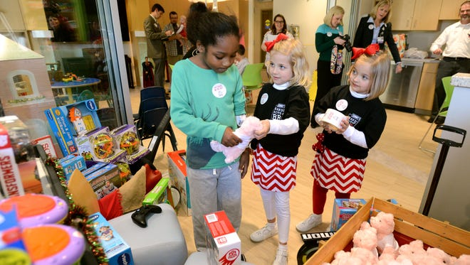 Kate, 7, and Caroline Johnson, 5, help Nasir Jennings, 8, pick out a toy and a stuffed animal at the Sacred Heart Children's Hospital. The Johnson girls raised over $1,600 by selling donuts to buy toys for children in need. They used the leftover money to give toys out to children at the hospital. The girls were recognized by Sonny's BBQ, as part of their Random Acts of BBQ program, and were awarded a BBQ feast. The Johnson family decided to pay the meal forward to doctors, nurses and staff at the children's hospital.