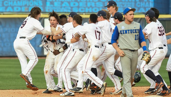 Auburn teammates mob freshman Edouard Julien in celebration after his walk-off hit in a 4-3 win over Kentucky in the Southeastern Conference Tournament in Hoover.