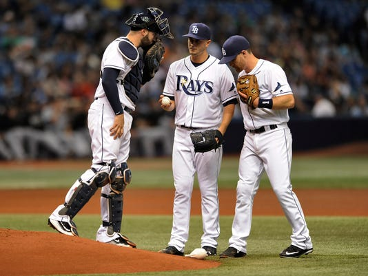 Tampa Bay Rays catcher Curt Casali, left, and infielder Logan Forsythe, right, talk with starter Jake Odorizzi on the mound during the fourth inning of a baseball game against the Chicago White Sox, Friday, April 15, 2016, in St. Petersburg, Fla. (AP Photo/Steve Nesius)