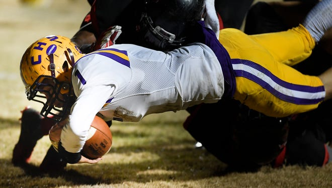Covington quarterback Brock Lomax (1) dives into the end zone for a touchdown past a Pearl-Cohn defender during the second half at Pearl-Cohn High School Friday, Nov. 24, 2017 in Nashville, Tenn.