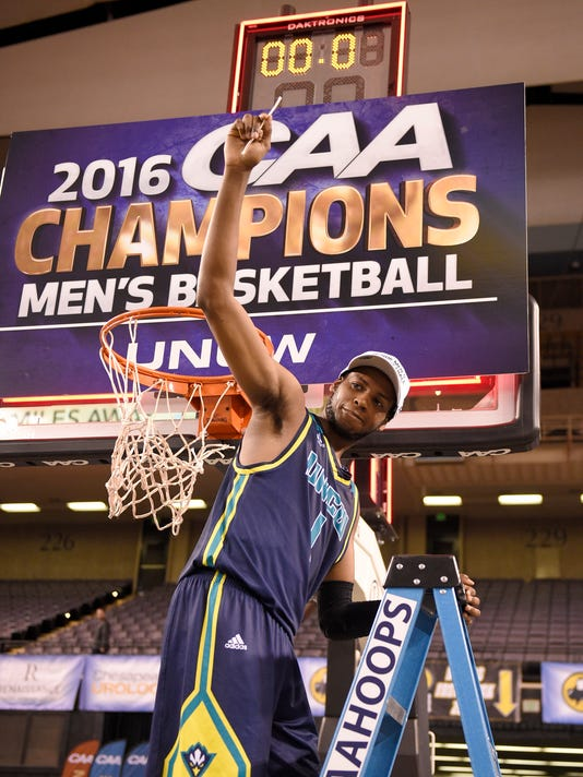 UNC Wilmington guard Chris Flemmings (1) holds up a piece of the net after an NCAA college basketball game in the Colonial Athletic Association Championship against Hofstra, Monday, March 7, 2016, in Baltimore. UNC Wilmington won 80-73 in overtime. (AP Photo/Nick Wass)