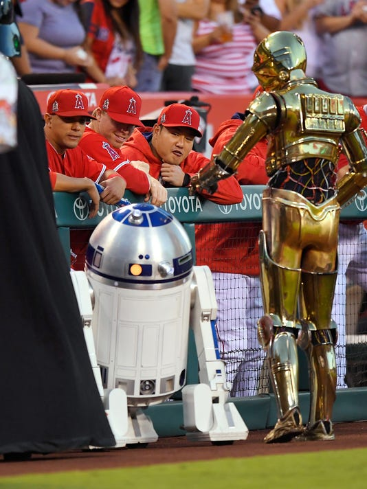 "Members of the Los Angeles Angels looks at characters from ""Star Wars""  prior to a baseball game against the Texas Rangers, Friday, Sept. 9, 2016, in Anaheim. The characters were on hand for Star Wars Night at Angels Stadium. (AP Photo/Mark J. Terrill)"