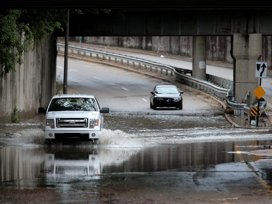 Automobiles brave a flooded stretch of North Parkway under Watkins after a severe thunderstorm knocked out power to most of Memphis Saturday night