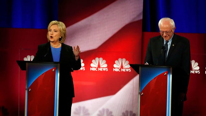 Democratic presidential candidate, Hillary Clinton, left,  speaks, as Democratic presidential candidate, Sen. Bernie Sanders, I-Vt, listens during the NBC, YouTube Democratic presidential debate at the Gaillard Center, Sunday, Jan. 17, 2016, in Charleston, S.C.