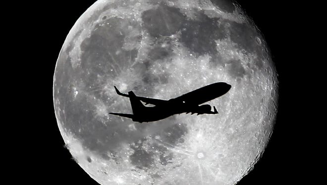 A United Airlines passenger plane crosses the waning gibbous moon, one day after a full moon, late Thursday, July 2, 2015, in Whittier, Calif. There will be two full moons in July, the next one known as a  blue moon, will be on July 31.