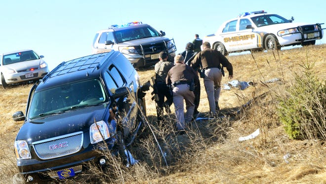Marathon County Sheriff's Department officials take a driver into custody at a ditch off of Highway 51 behind Texas Roadhouse in Rib Mountain Tuesday, March 17, 2015. Authorities say the arrest occurred after a high-speed chase involving multiple law enforcement agencies.