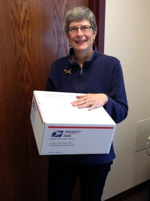 Lori Wiederhoeft with box of stamps ready to ship from the Holy Cross Sisters office in Merrill to India.