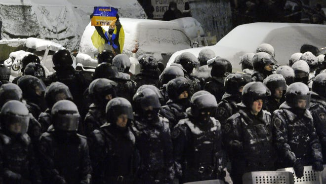 A Pro-European protester holds placard reading 'Ukraine begins from you!' in front of riot police guarding the presidential office in Kiev on December 9, 2013.