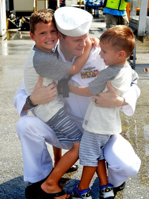 Electrician's Mate 1st Class Jeffrey Pass hugs his sons Rory and Liam during a homecoming celebration for the Los Angeles-class attack submarine USS Topeka on Jan. 28, following a two-month forward operating period to the Western Pacific.