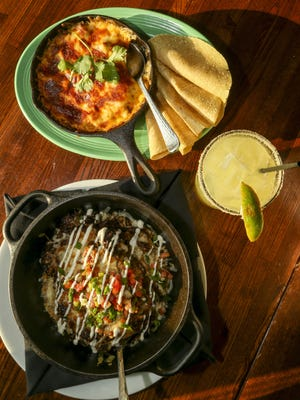 Dos Rios serves the queso fundido dip (top) with chips and the molcajete entre (bottom) with a margarita on the rocks.