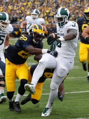 Michigan State's LJ Scott runs out of the tackles of Michigan's Jarrod Wilson , left, and Delano Hill, back, for a touchdown to tie the game 7-7 on Saturday, October 17, 2015, in Ann Arbor. Julian H. Gonzalez/Detroit Free Press
