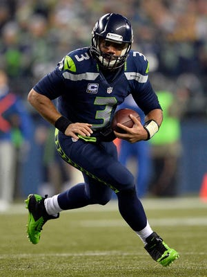 Seattle Seahawks quarterback Russell Wilson (3) runs the ball against the Carolina Panthers during the second half in the 2014 NFC Divisional playoff football game at CenturyLink Field.