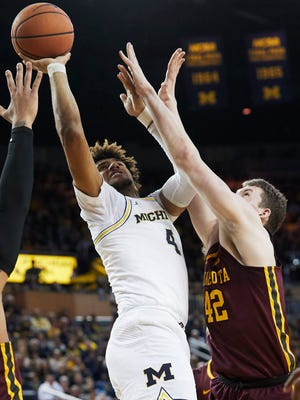 Feb 3, 2018; Ann Arbor, MI, USA; Michigan Wolverines forward Isaiah Livers shoots over Minnesota Golden Gophers forward Michael Hurt (42) in the first half at Crisler Center.